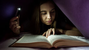 Young woman hiding under blanket and enrapt reading interesting book at nighttime. Girl lighting with the phone as a Royalty Free Stock Photos