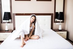 Young woman hiding under blanket. Lady smiling Let`s play hide and seek. Royalty Free Stock Photography