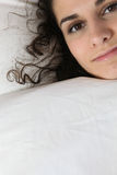 Young woman hiding under duvet Royalty Free Stock Photography