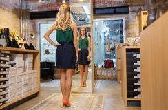 Young woman in high-heeled shoes at store mirror Stock Photos