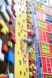 Young woman on high rock-climbing wall Royalty Free Stock Image