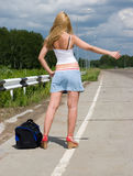 Young woman on highway. Young woman stops a car on highway Stock Images