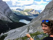 A young woman hiker admiring the view from the side of the mountain. Down below is the Rockies and upper Kananaskis lake stock photo