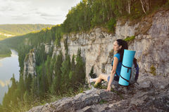 Young woman hiker with backpack sitting on edge of cliff at high altitude Royalty Free Stock Images