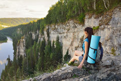 Young woman hiker with backpack sitting on edge of cliff at high altitude Stock Images