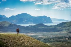 Young woman hiker with backpack standing in a Crimea valley Royalty Free Stock Image