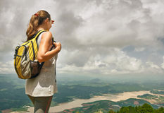 Young woman hiker with backpack standing on top of the mountain Stock Photo