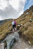 Woman backpacker hiking on a trail Stock Photo