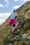 Woman backpacker hiking on a trail Royalty Free Stock Photography