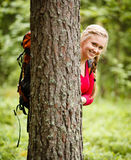 Young woman hiker behind a tree Royalty Free Stock Photography