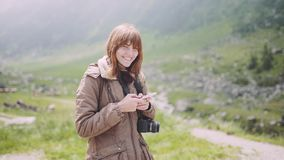 A young woman hiker climbs mountains with camera and use smartphone. Transfagarasan, Carpathian mountains in Romania. A young woman hiker climbs mountains with stock footage