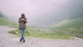 A young woman hiker climbs mountains with camera and use smartphone. Transfagarasan, Carpathian mountains in Romania. A young woman hiker climbs mountains with stock video footage