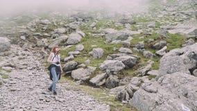 A young woman hiker climbs mountains with photo camera. Transfagarasan, Carpathian mountains in Romania. A young woman hiker climbs mountains with photo camera stock video footage