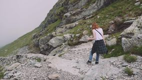 A young woman hiker climbs mountains with photo camera. Transfagarasan, Carpathian mountains in Romania. A young woman hiker climbs mountains with photo camera stock video