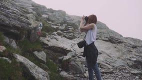 A young woman hiker climbs mountains with photo camera. Transfagarasan, Carpathian mountains in Romania. A young woman hiker climbs mountains with photo camera stock footage