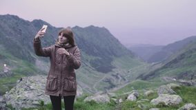 A young woman hiker climbs mountains and does selfie on smartphone camera. Transfagarasan, Carpathian mountains in Romania. A young woman hiker climbs mountains stock video