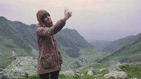 A young woman hiker climbs mountains and does selfie on smartphone camera. Transfagarasan, Carpathian mountains in Romania. A young woman hiker climbs mountains stock video footage