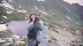 A young woman hiker climbs mountains and photographs landscapes on camera. Transfagarasan, Carpathian mountains in Romania. A young woman hiker climbs mountains stock footage