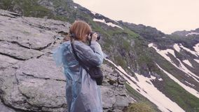 A young woman hiker climbs mountains and photographs landscapes on camera. Transfagarasan, Carpathian mountains in Romania. A young woman hiker climbs mountains stock video footage