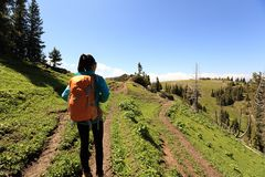 Woman hiker hiking on mountain top trail. Young woman hiker hiking on mountain top trail Royalty Free Stock Photo