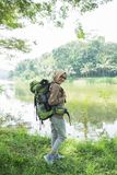 Woman hiker hiking on mountain trail. Young woman hiker hiking on mountain trail. Travel concept. Happy traveler with backpack Stock Photo