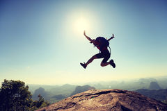 Young woman hiker jumping on mountain peak. Cheering successful young woman hiker jumping on mountain peak Royalty Free Stock Photography