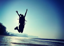 Young woman hiker jumping on sunrise beach Royalty Free Stock Images
