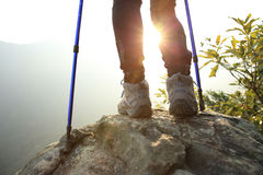 Young woman hiker legs on sunrise mountain peak Stock Images