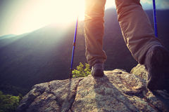 Young woman hiker legs on sunrise mountain peak Stock Image