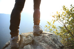 Young woman hiker legs on sunrise mountain peak Royalty Free Stock Images