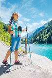 Young woman hiker in mountains with a telescope Stock Image