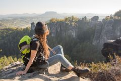 Young woman hiker in the mountains. Young woman traveler with baclpack stand on the cliff in mountains royalty free stock images
