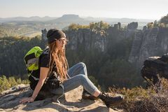 Young woman hiker in the mountains. Young woman traveler with baclpack stand on the cliff in mountains stock photography