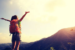 Young woman hiker open arms at mountain peak Stock Photography
