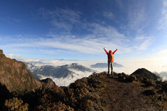 Young woman hiker open arms on mountain peak Stock Photos