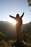 Young woman hiker open arms on mountain peak Stock Photo