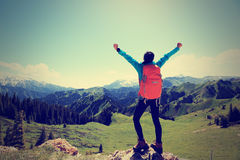 Young woman hiker open arms on mountain top Stock Photos
