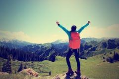 Young woman hiker open arms on mountain top Stock Photos