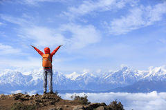 Young woman hiker open arms to beautiful snow mountain summits Stock Images