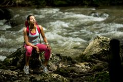 Young woman hiker rests next to the river. Young woman hiker rests next to the forest river Royalty Free Stock Image