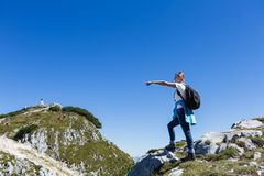 Hiker on mountain pointing. Young woman hiker with rucksack in good weather on rocky mountain  pointing across a ravine into the distance Royalty Free Stock Images