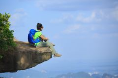 Woman hiker sit on mountain top cliff enjoy the view. Young woman hiker sit on mountain top cliff enjoy the view Royalty Free Stock Photography