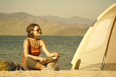 Young woman hiker sit near the tent and looking on sea landscape Royalty Free Stock Images