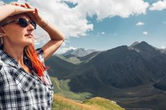 Young Woman Hiker Standing On Cliff And Enjoy The View Mountain In Summer. A young woman with glasses raised her hands to her head, stands on the top of the royalty free stock image