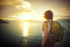 Young woman hiker standing on the coast and enjoying sunset over Stock Images