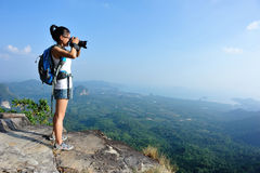 Young woman hiker taking photo with dslr camera Stock Image