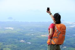 Woman hiker taking photo with smartphone on mountain peak Royalty Free Stock Images