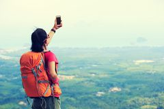 Woman hiker taking photo with smartphone on mountain peak Stock Images