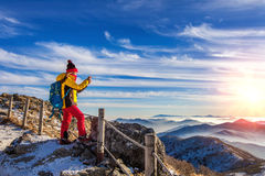 Young woman hiker taking photo with smartphone on mountains peak. Royalty Free Stock Photography