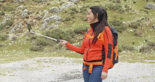 Young woman hiker using a selfie stick stock video footage